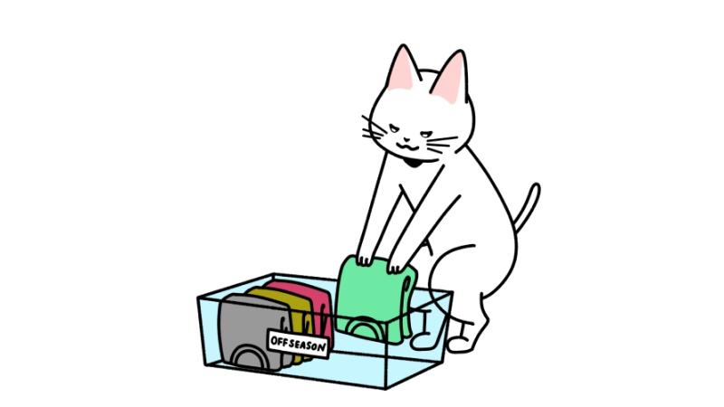 衣替えでオフシーズンの服を整理する猫のイラスト